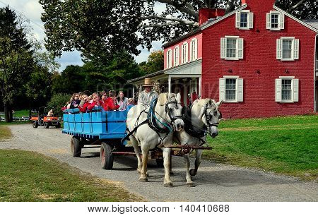 Lancaster Pennsylvania - October 14 2015: School children enjoy riding in a wooden wagon pulled by two white horses driven by a straw hat wearing driver at the Landis Valley Village and Farm Museum
