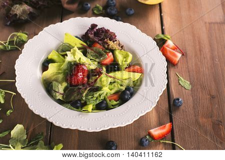 Fresh summer salad with mix of berries, arugula, lettuce, spinach and chard