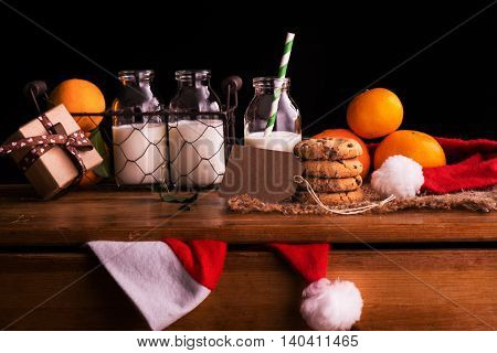 Christmas composition with milk and cookies for Santa Claus. Xmas card in dark tones. Selective focus