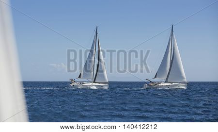 Sailing luxury yachts in the open sea in calm weather.