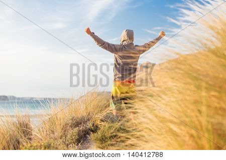 Successful sporty active man, arms rised, enjoying beauty of nature, freedom and life at beautiful landscape at Balos beach, Greece. Active lifestyle outdoors. Made it.