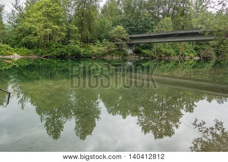 A bridge and trees are reflected in a river in North Bend Washington.