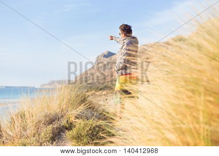 Sporty active man pointing hand on horizon, enjoying beauty of nature, freedom and life at beautiful landscape. Active lifestyle outdoors.
