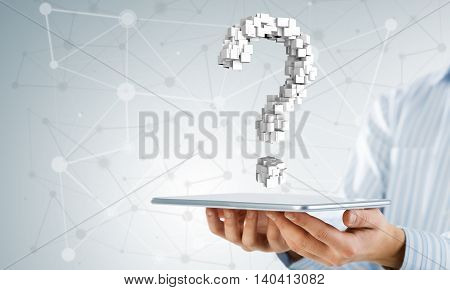 Close up of businessman hand holding tablet with question sign