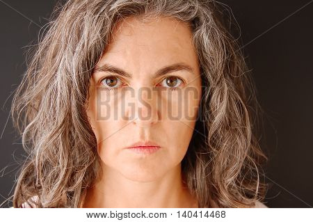 Woman on black background facing the camera