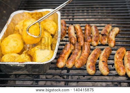 Sausage, hot dogs and potatoes on grill. Cooking in the nature. Grillparty