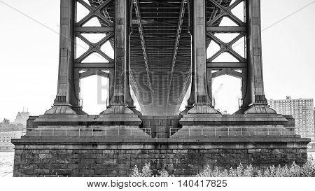 A black and white shot taken from underneath the Manhattan Bridge.