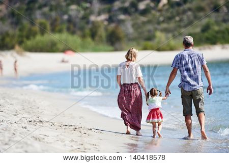 Family with little child on sea beach