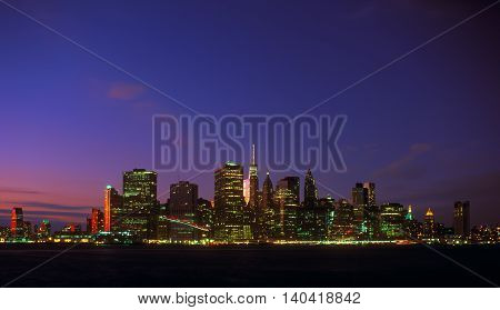 New York City skyline at night with blue sky and illuminated buildings.