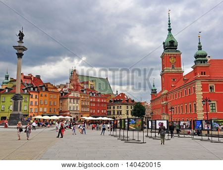 WARSAW POLAND - JUNE 13: Tourists walking by Warsaw town square on June 13 2014. Warsaw is a capital and largest city of Poland.