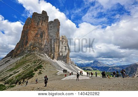 TRE CIME ITALY - JULY 12: Tourists goes by the path around Three Peaks mountain range Italy on July 12 2014. Three Peaks is a national park in Veneto province in northern Italy.