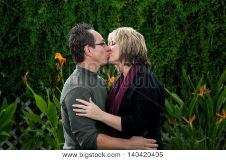 A middle aged couple shows their love for one another with a kiss.