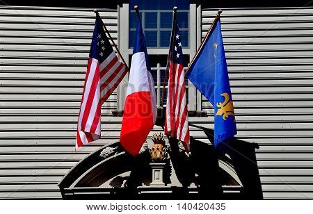 Newport Rhode Island - July 16 2015: American French and Canadian flags fly above the East front doorway of the 1748 colonial Georgian Hunter House at Easton's Point historic district