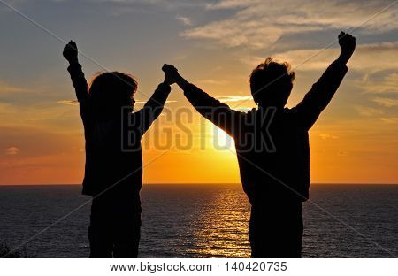Two boys on sunset with the hands up