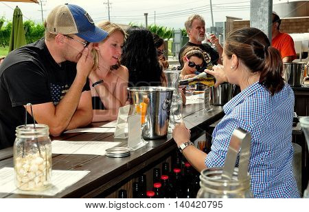 Middletown Rhode Island - July 18 2015: Bar tender pouring a bottle of white wine for a young couple to taste at the Newport Winery Vineyard