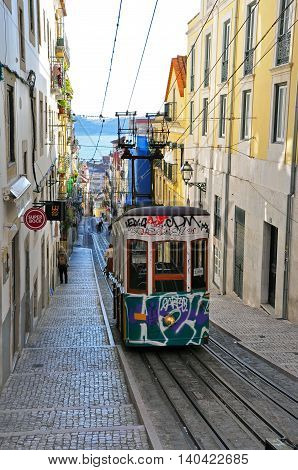LISBON PORTUGAL - NOVEMBER 24: Old painted funicular goes up the street in Lisbon city on November 24 2013. Lisbon is the capital and the largest city of Portugal.