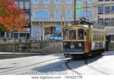 PORTO PORTUGAL - NOVEMBER 26: Retro tram number 18 goes by the street of Porto historical centre on November 26 2013. Porto is one of the oldest European centers and the second largest city of Portugal.