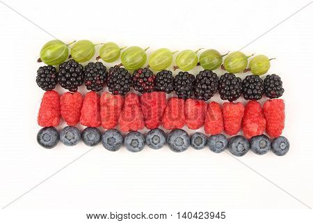 raspberries gooseberries blackberries and blueberries in rows on a white background