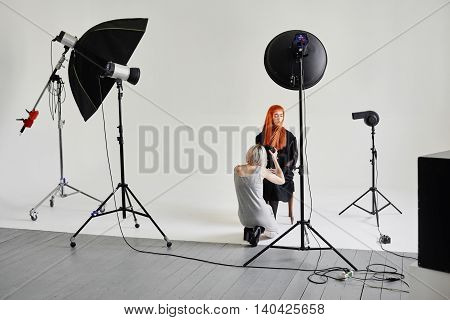 Girl photographer photographing fashion model in black sitting on a chair on white background in Studio