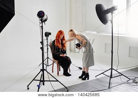 The photographer straightens hair fashion model sitting on chair on white background in Studio