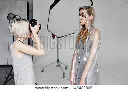 Girl photographer photographing fashion model in transparent coat with pomegranate mask on her face on white background in Studio