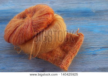 Knitting orange mohair wool on wooden blue rustic background. The beginning on knit cloth