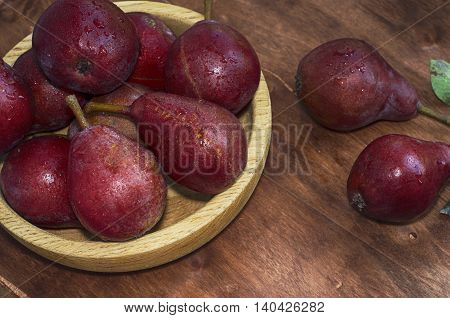 Ripe red pear in a wooden plate on the table