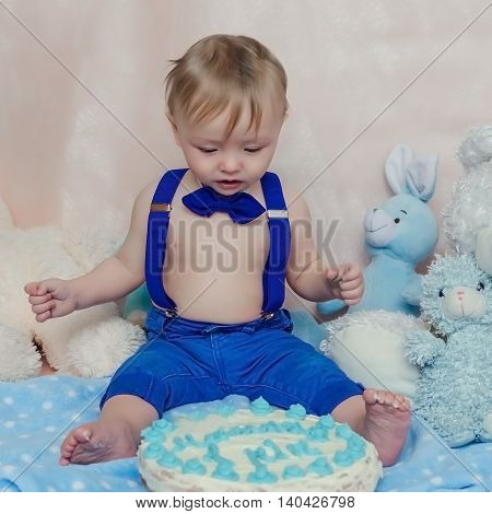 Baby boy gets to eat cake for the first time on his first birthday. Little baby boy in blue pants suspenders and bow tie without shirt sitting and looking confusedly with funny face.