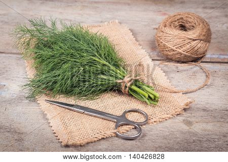Dill tied in a bun on a wooden surface and a napkin from jute cord and scissors