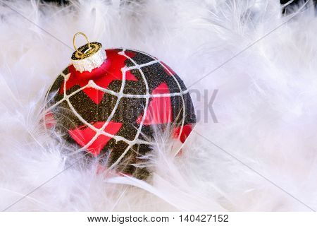 Christmas ornament sitting in a bed of fluffy white feathers.