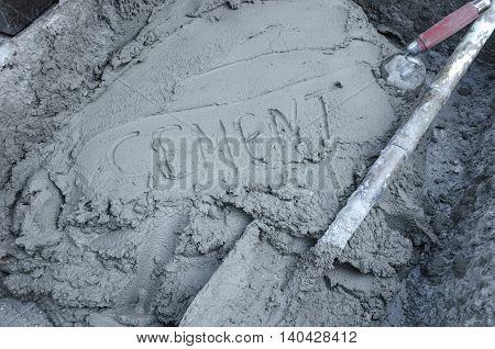 Inscription the word cement on cement with trowel