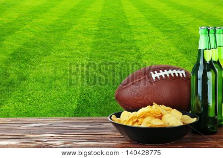 Beer bottles, ball and snack on football field background