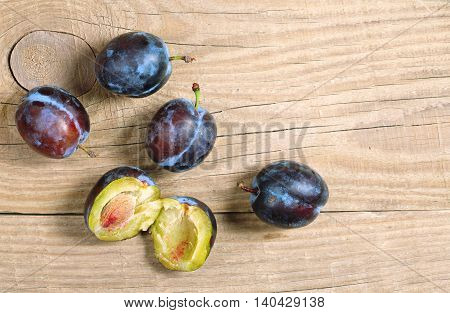 Ripe plums on wooden background top view