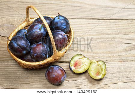Ripe plums in basket on wooden background