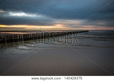 Sunset on beach with a wooden breakwater in Leba Baltic Sea Poland