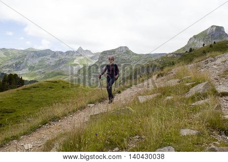 happy girl hiking the mountains in Pyrenees France with her hiking sticks