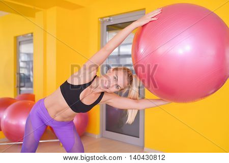 fitness, sport, training and lifestyle concept - happy woman exercising with ball in gym.