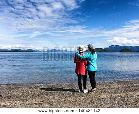 Daughter and mother facing away from camera enjoying the outdoors on a beautiful lake with mountains and sky in background.