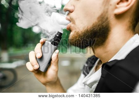 Man with beard and smoke. Thick steam. Bicycle. Vape.