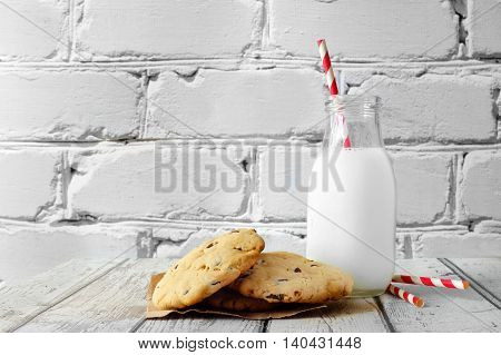 Milk In Traditional Bottle With Chocolate Chip Cookies Against A White Brick Background