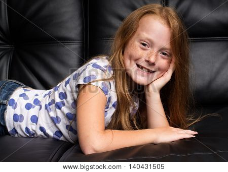Little ginger girl with freckles laying on the black leather sofa and smiling