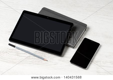 Business kit - a tablet a notebook a pencil and a mobile telephone on white wooden surface