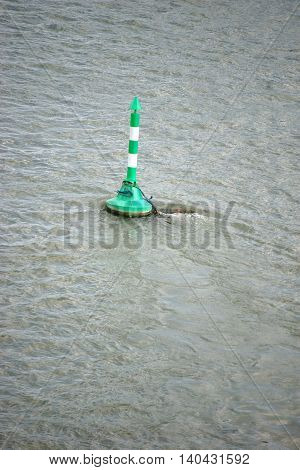 A green and white striped buoy on a river near an inland port.