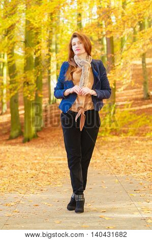 Young female in forest. Girl taking walk through park in autumn. Nature fashion relax concept.