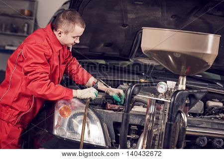 Automobile engine oil replacement. Auto repair worker serviceman replacing lubricating motor liquid by pump at garage