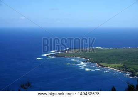 Waves roll towards Kalaupapa Peninsula with airport and Lighthouse in view on Molokai which is the site of Saint Damiens mission where he ministered for 16 years to those suffering from Hansen disease. Seen from lookout.
