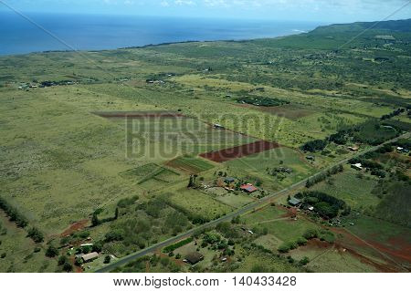 Aerial of Farm fields of different stages of age and homes running to the ocean on Molokai Hawaii. April 2016.