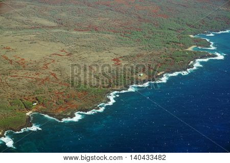 Aerial of Northwest coast of Molokai with waves crashing into shore and surrounding area of island with roads largely undeveloped. April 2016.
