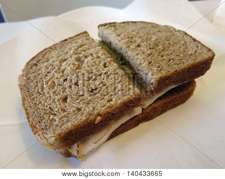 Turkey Sandwich with avocado on Whole Wheat Bread on white paper.