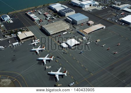 HONOLULU - APRIL 18: Aerial view of planes helicopters and cars parked by buildings at the Honolulu International Airport HNL next to the water on Oahu Hawaii. April 18 2016.